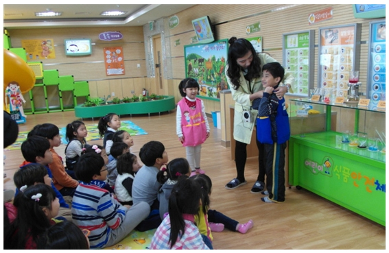 어린이 식품안전체험관의 프로그램에서 발표하는 어린이 및 이를 듣고 있는 어린이들의 모습이 담겨있는 사진