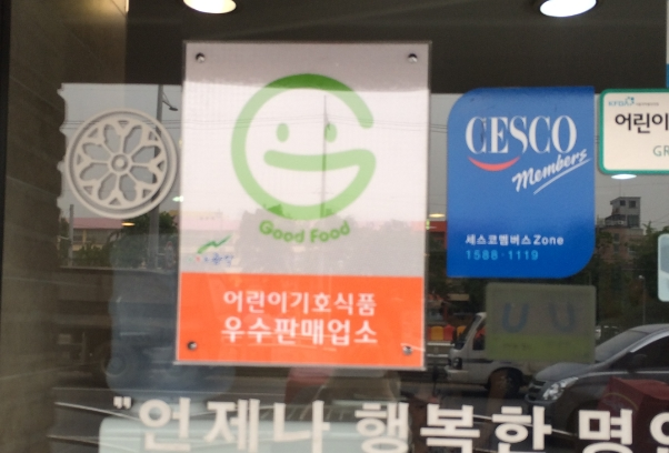 'Good Food'라고 적힌 웃는 얼굴 모양의 마크가 있는 어린이기호식품 우수판매업소 표시의 예